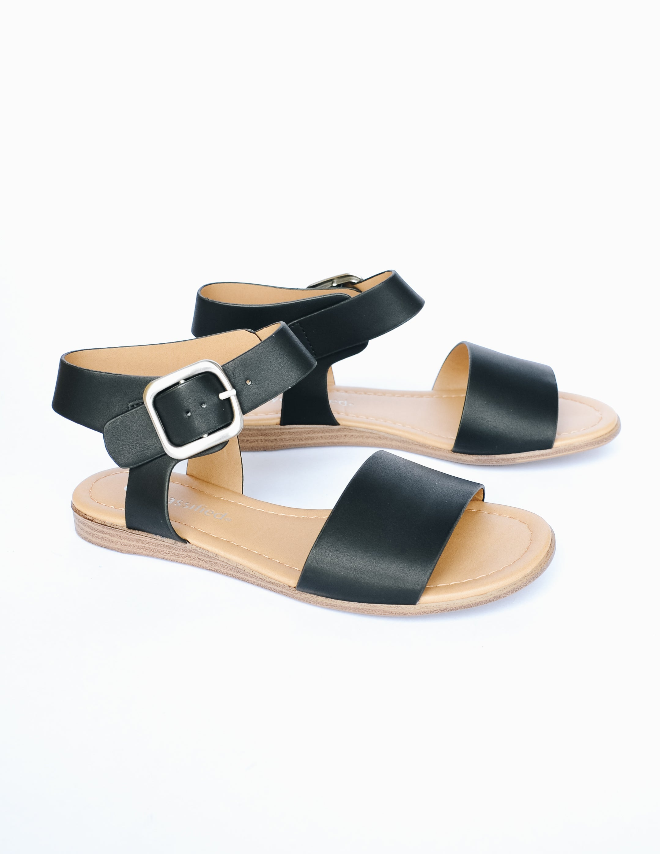 Black sandal with strap over toe and around ankle on faux wood sole