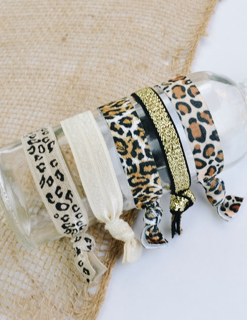 5 packs cheetah hair ties wrapped around clear glass bottle