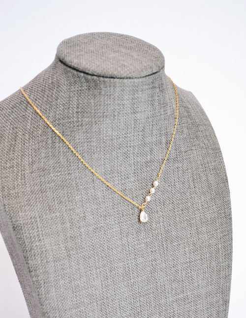Gold caprie necklace on form showing crystal pendant and pearls