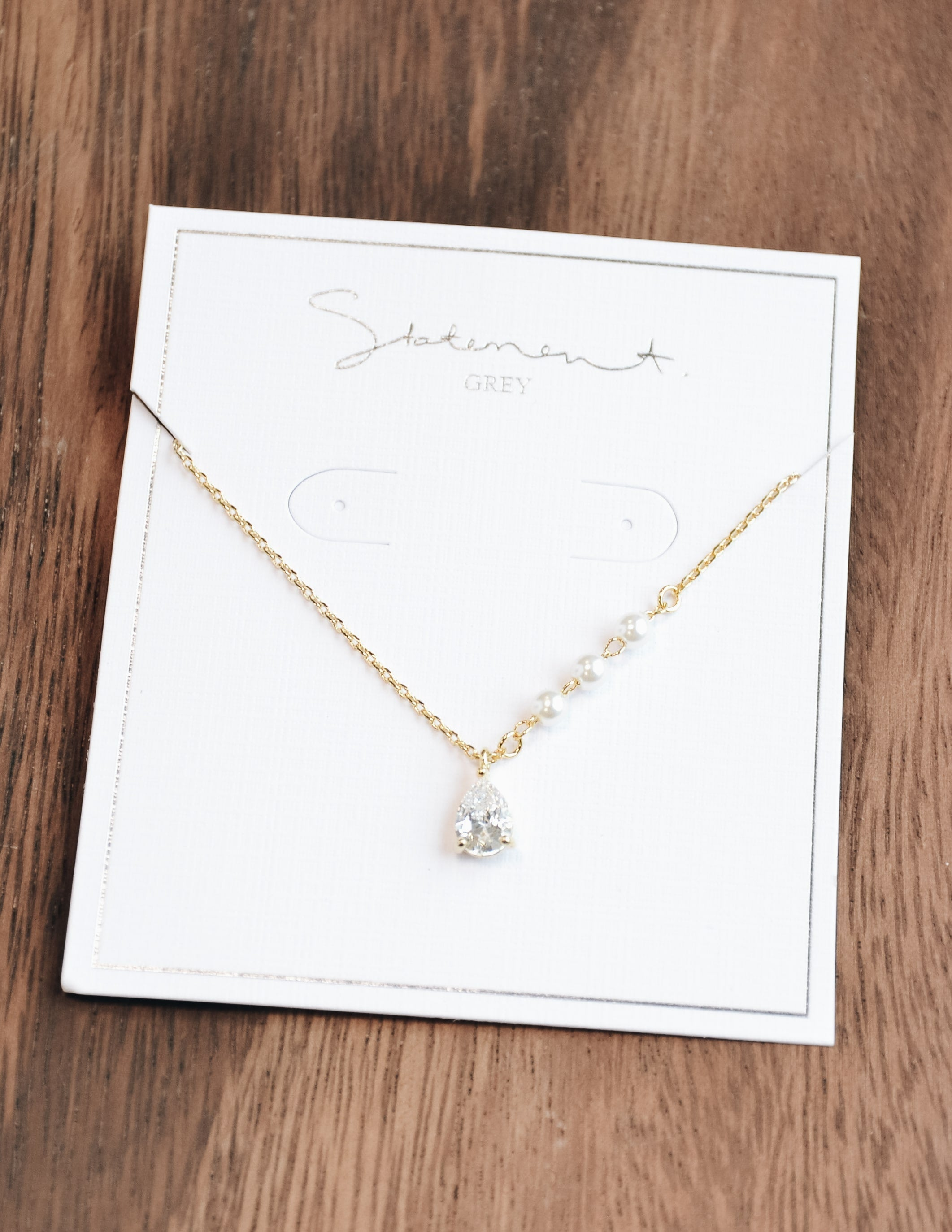 Gold Caprie necklace on white statement grey card - elle bleu
