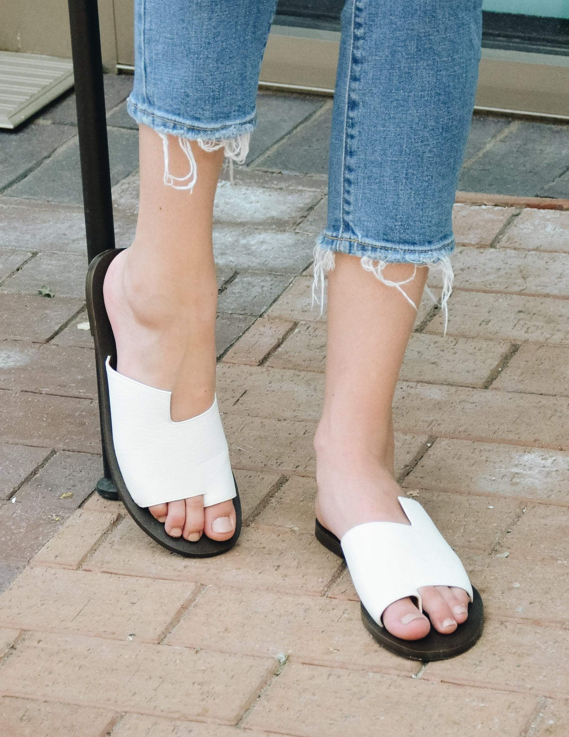 Close up of the model wearing white addison slides - Elle Bleu Shoes