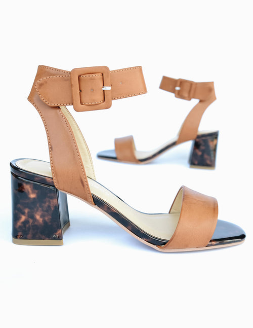 Tan upper and tortoiseshell heel and sole on beach side heel