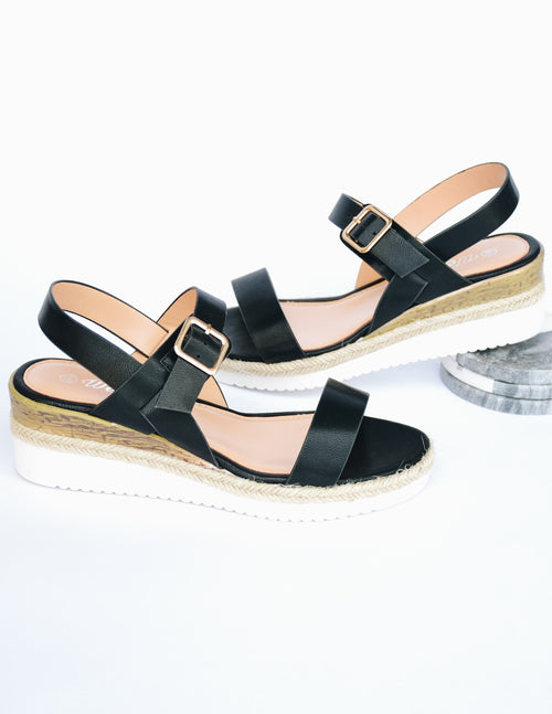 Black strap wedge sandal with white platform and faux wood detail