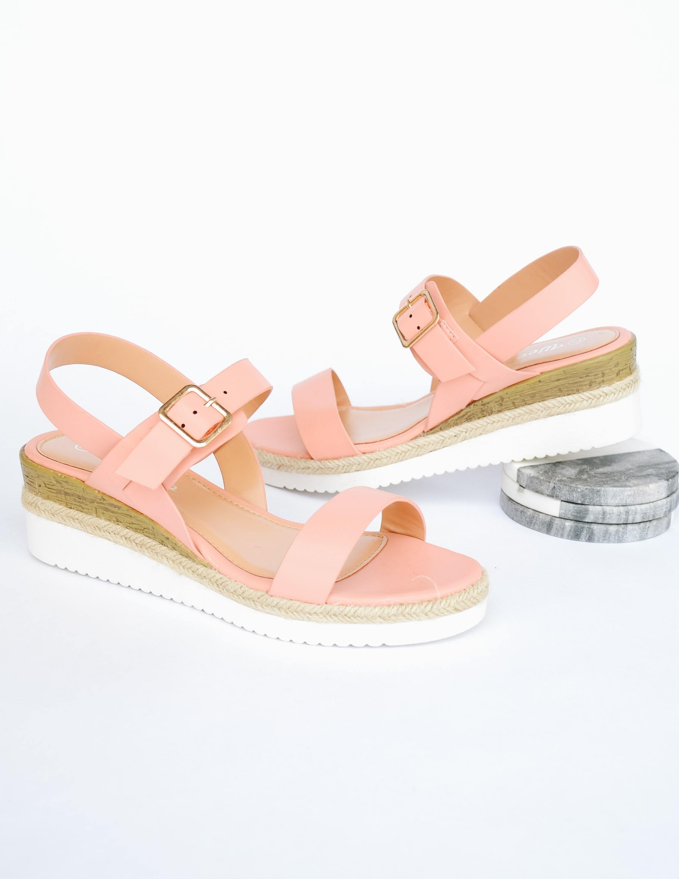 Pink straps on white platform wedge sole with faux wood detail