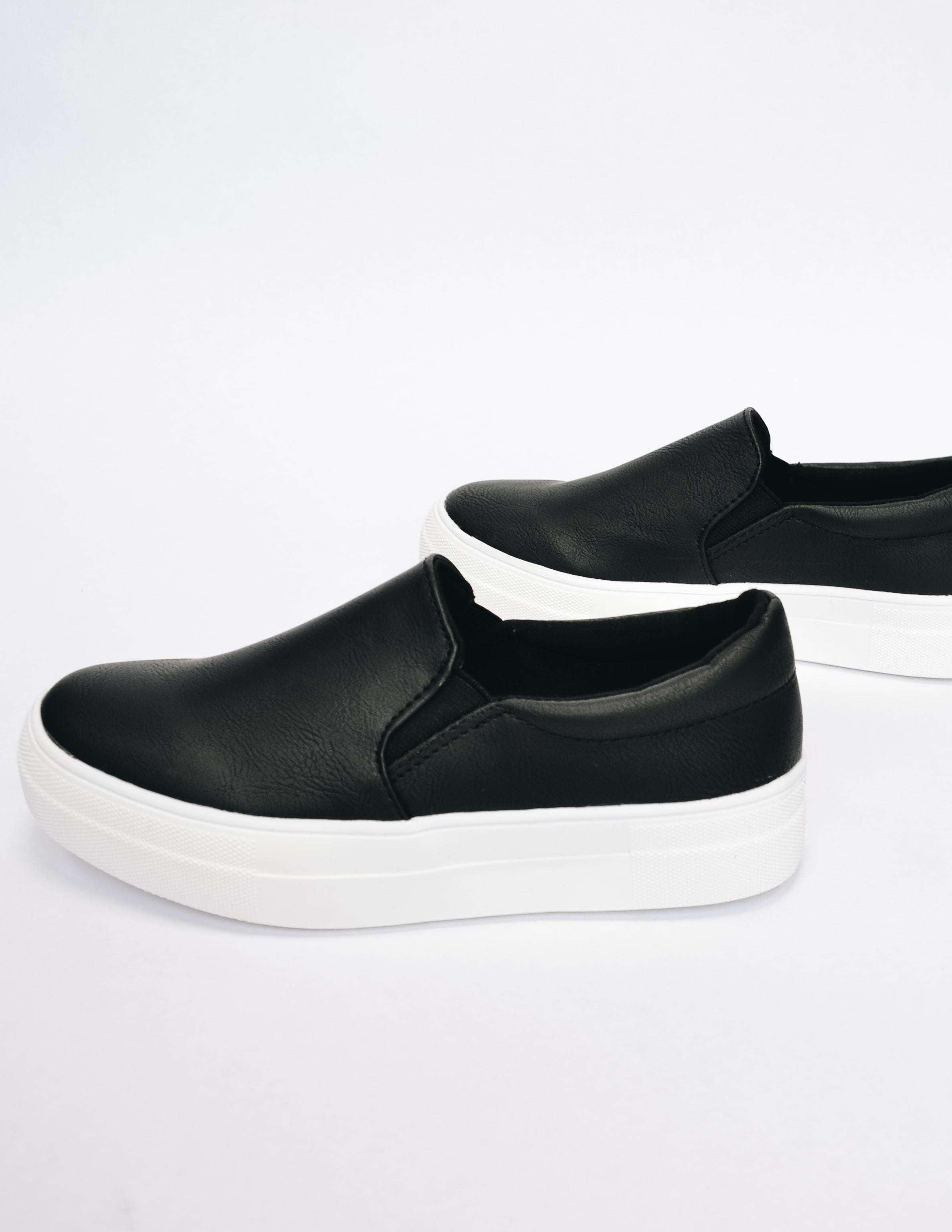 Side view of black slip on sneaker showing off elastic gores