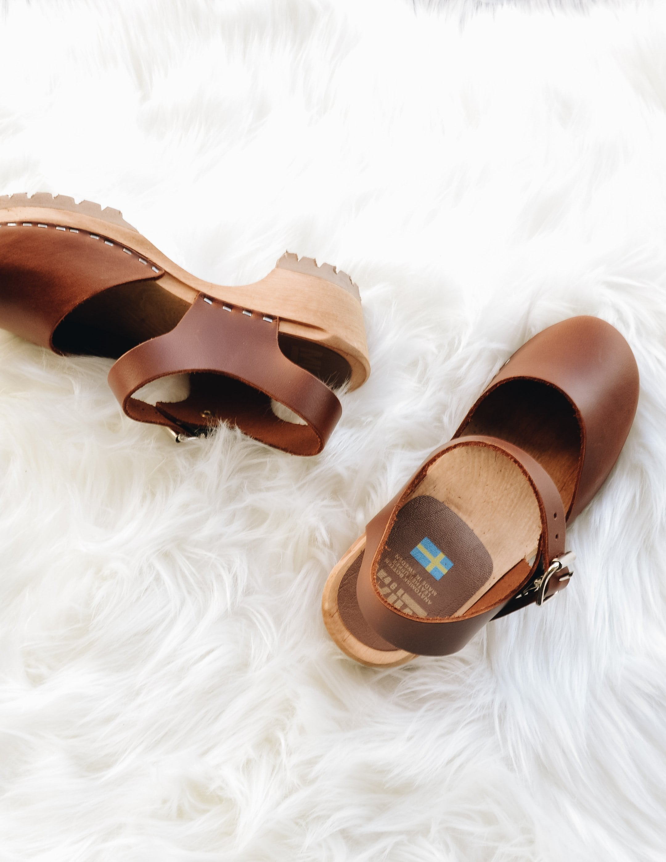 Luggage brown freja clogs laying down on white fur rug - elle bleu shoes