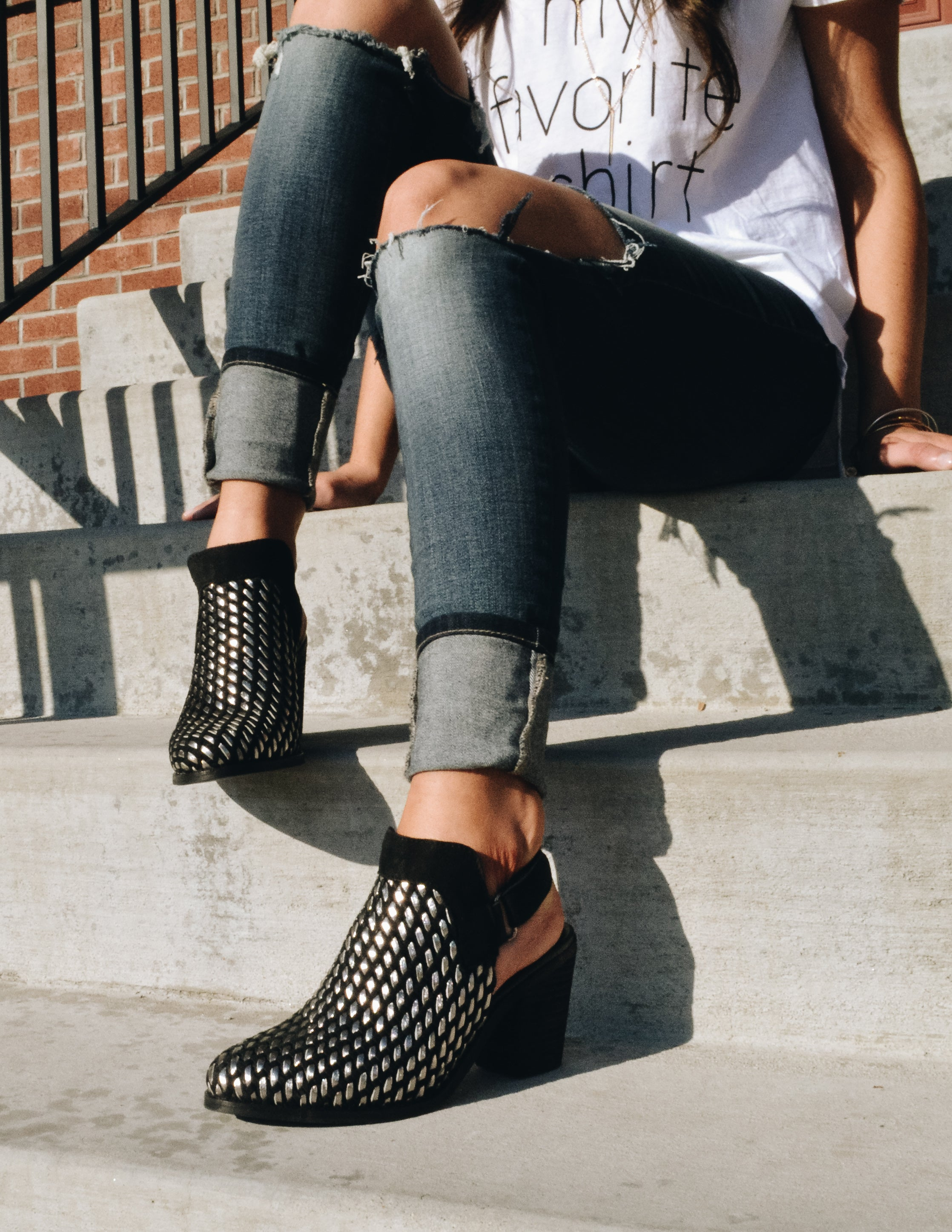 Model sitting on concrete steps wearing denim and black Sandara heel - Elle Bleu Shoe Boutique