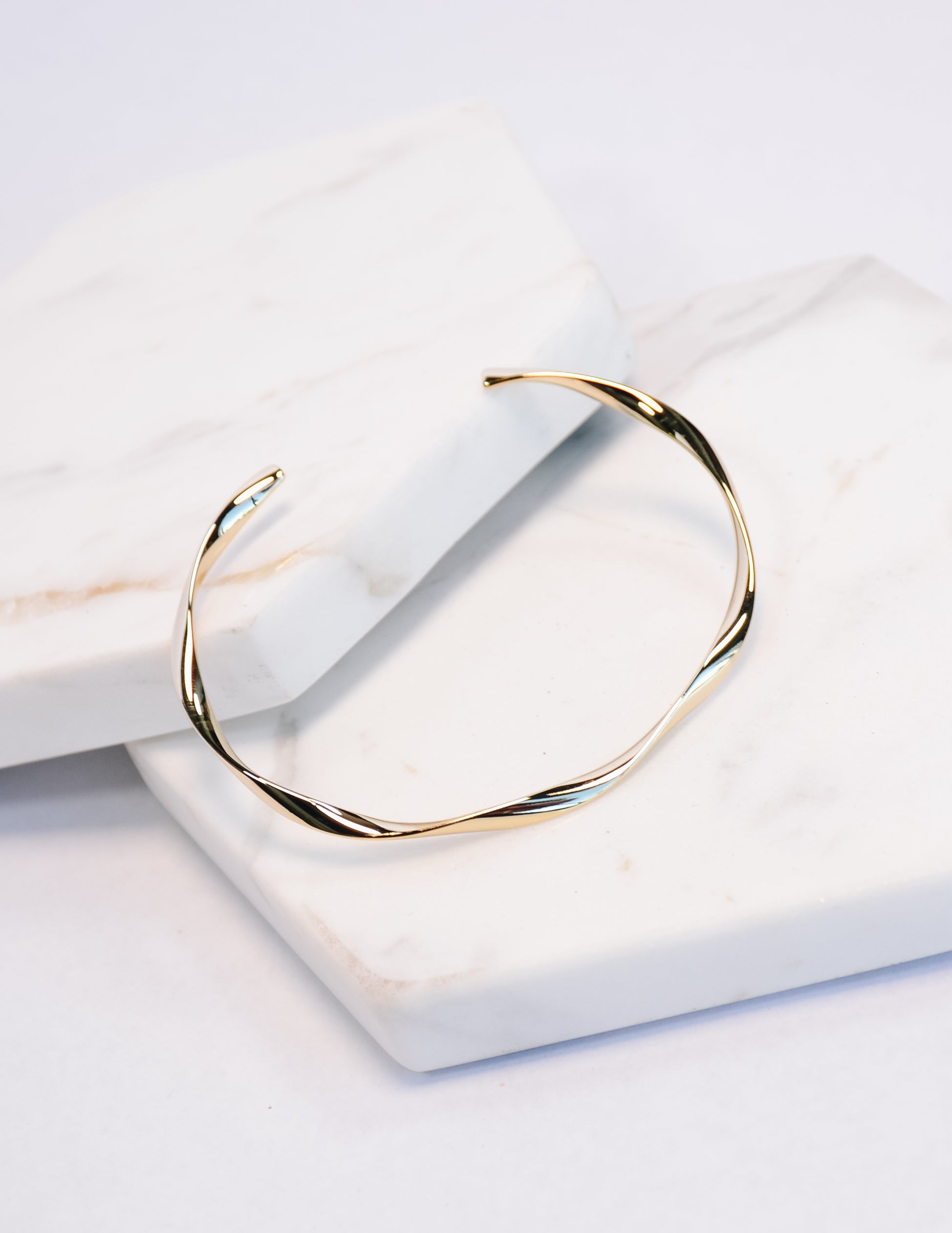 Lula gold bracelet on white stone background