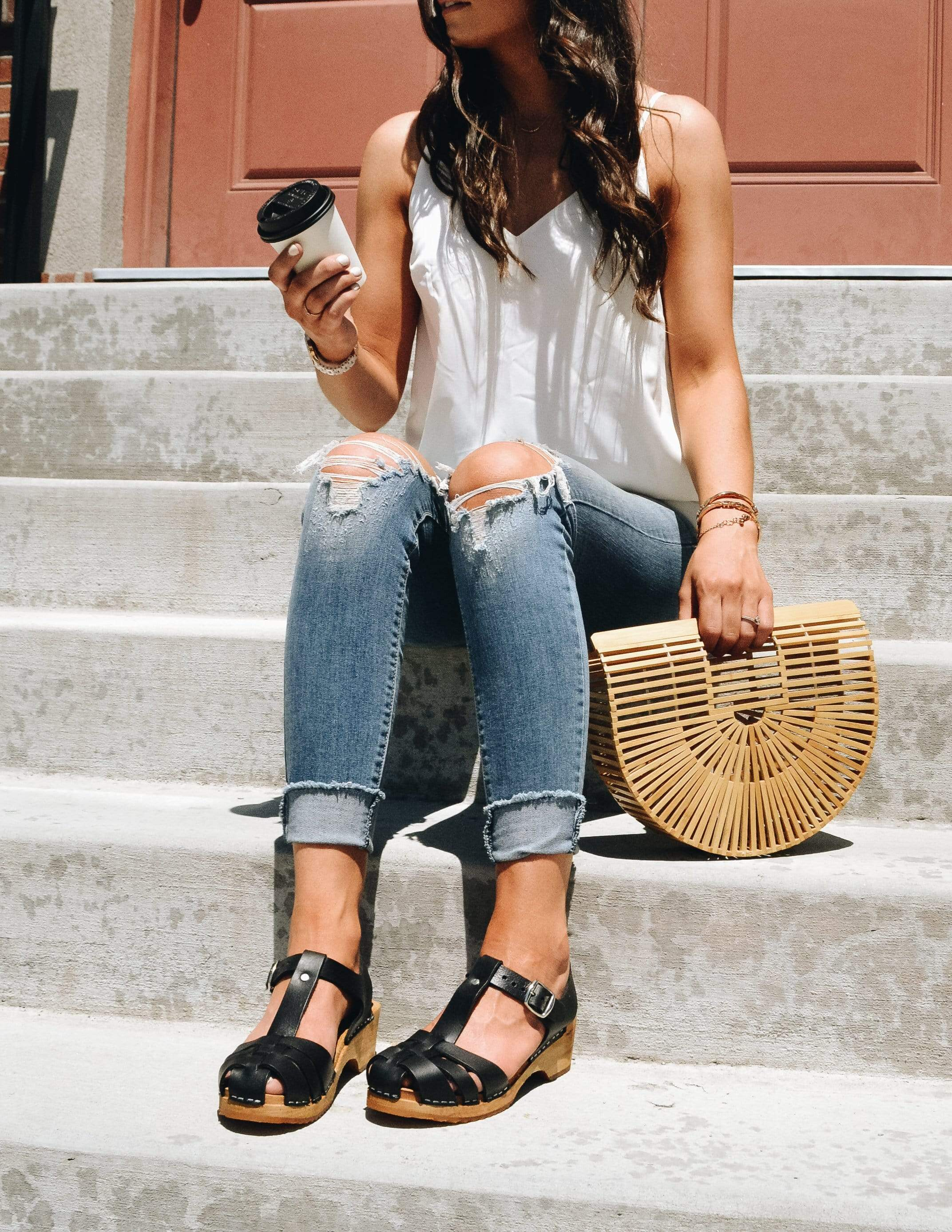 Model sitting outside holding coffee and bag wearing tank, denim and clogs