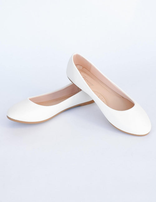 White flats stacked one heel on another on white background