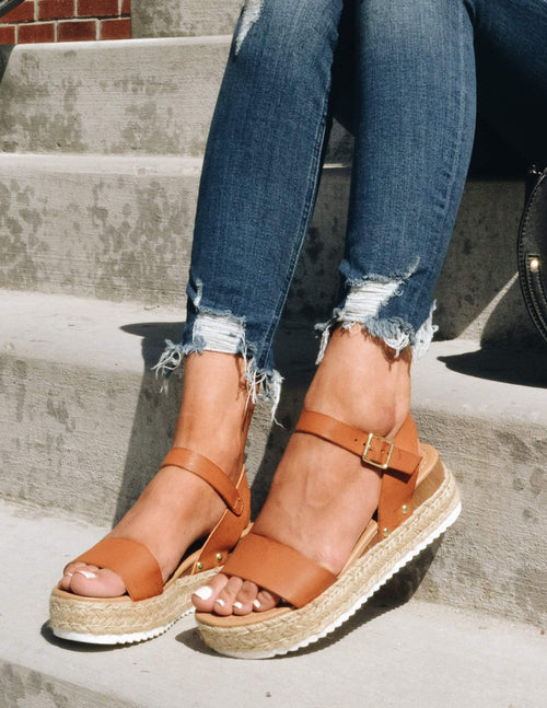 Closeup of model sitting on steps in tan strap platforms and denim