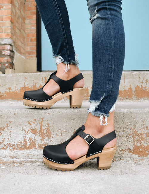 Black madeline clog with t strap upper, adjustable buckle, solid wood platform