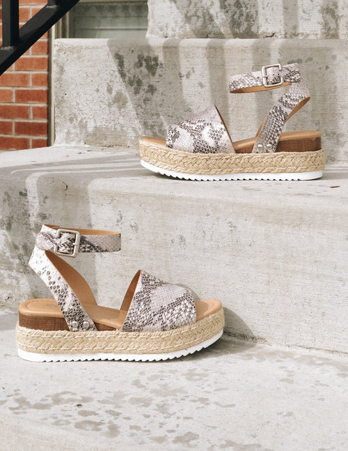 Grey snake print walkin on sunshine platforms outside on concrete steps