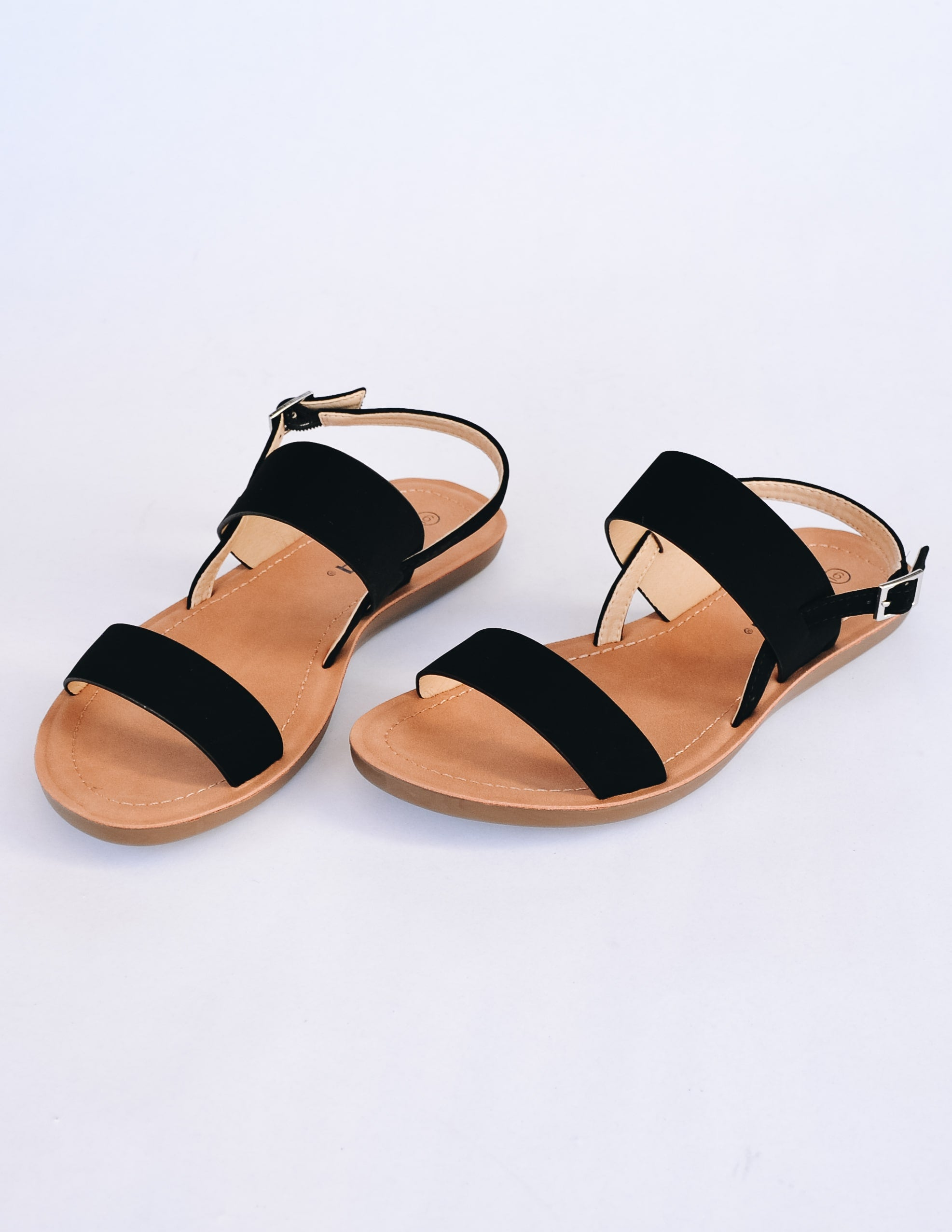 Black strappy sandals with tan insole on white background - elle bleu