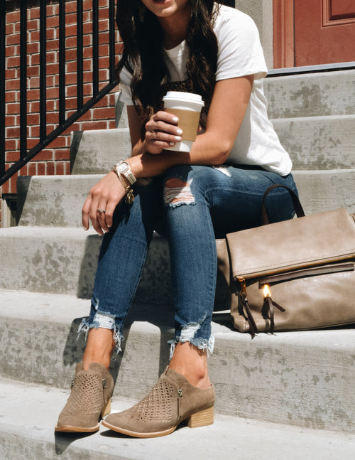 Model sitting on concrete steps holding coffee with taupe bag and booties - Elle Bleu Shoe Boutique