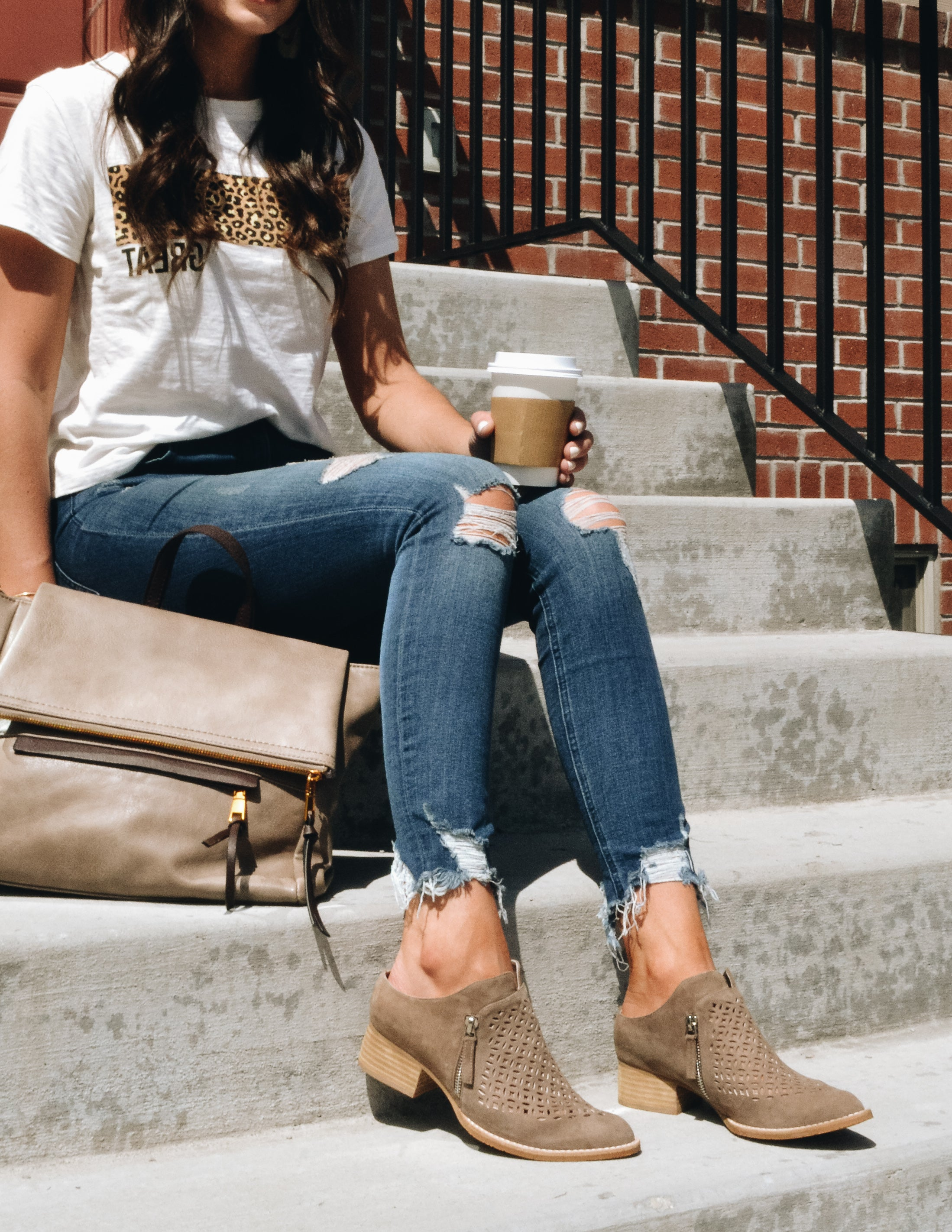 Model sitting on concrete steps holding coffee and taupe bag wearing denim and white tee