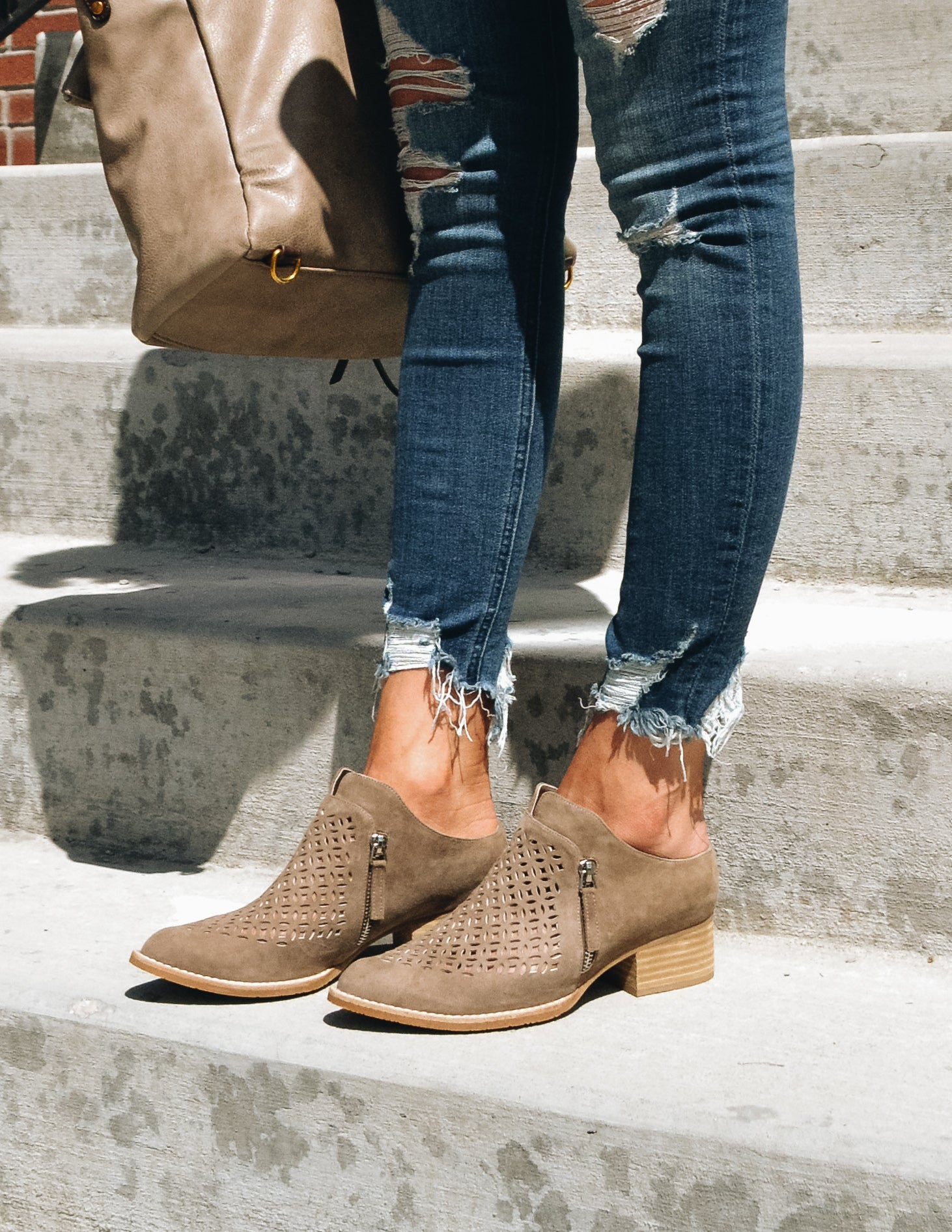 Woman standing on concrete step showing knee-down details of Taniss booties - Elle Bleu Shoe Boutique
