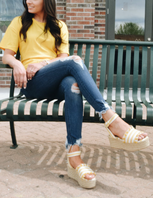 Model sitting on bench in yellow shirt, distressed denim and bigbang platform