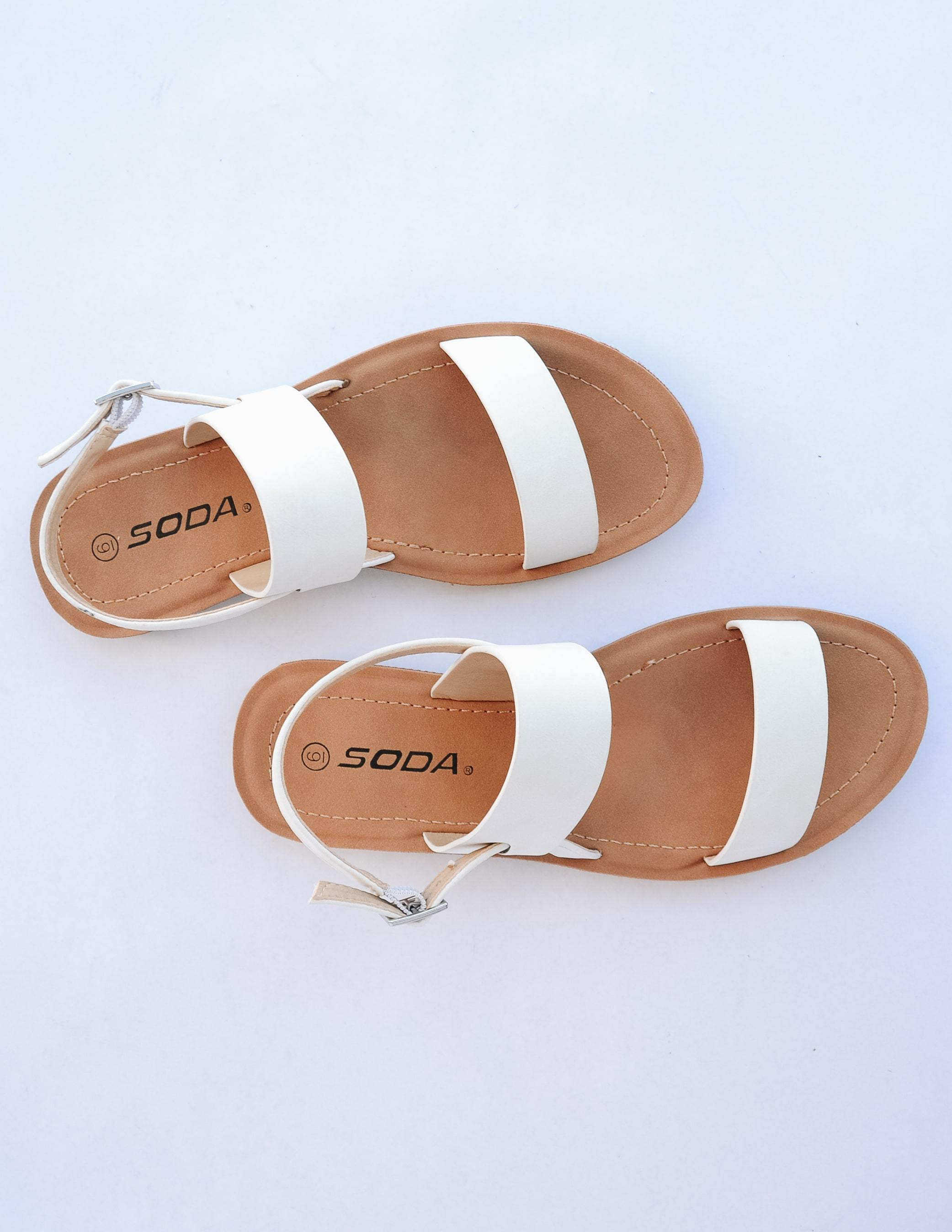Top view of the off white strappy sandal with tan insole