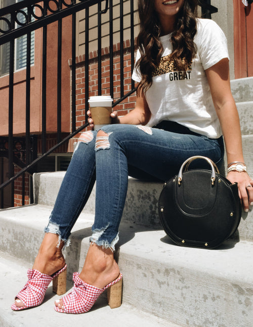 Model sitting outside on steps holding coffee, wearing denim, tee, and red alona heel