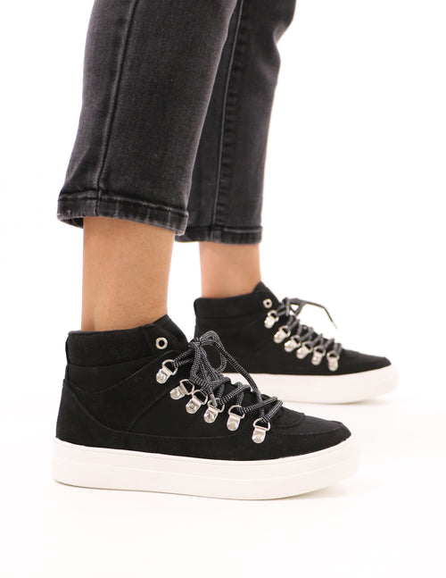 model standing in the black in the loop high top sneakers