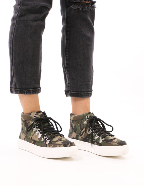 model standing in black denim and camo in the loop sneakers