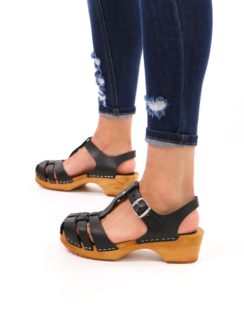 model standing in genuine wood and leather black mia like clogwork clogs and distressed denim - elle bleu