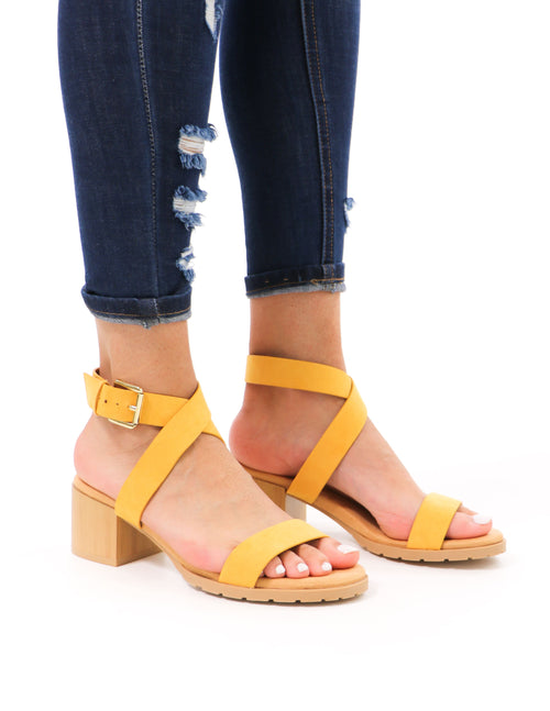 model standing in distressed denim and mustard saffron wrap out of it block qupid heels - elle bleu