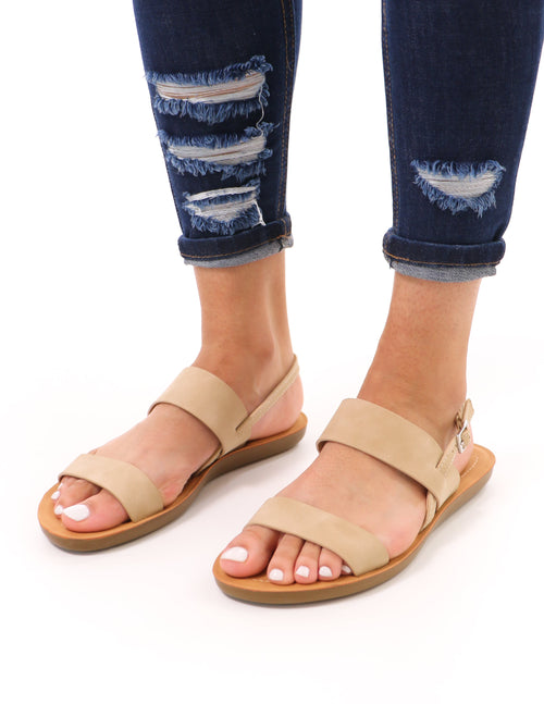 model standing in taupe soda sand then some slingback sandal and distressed denim
