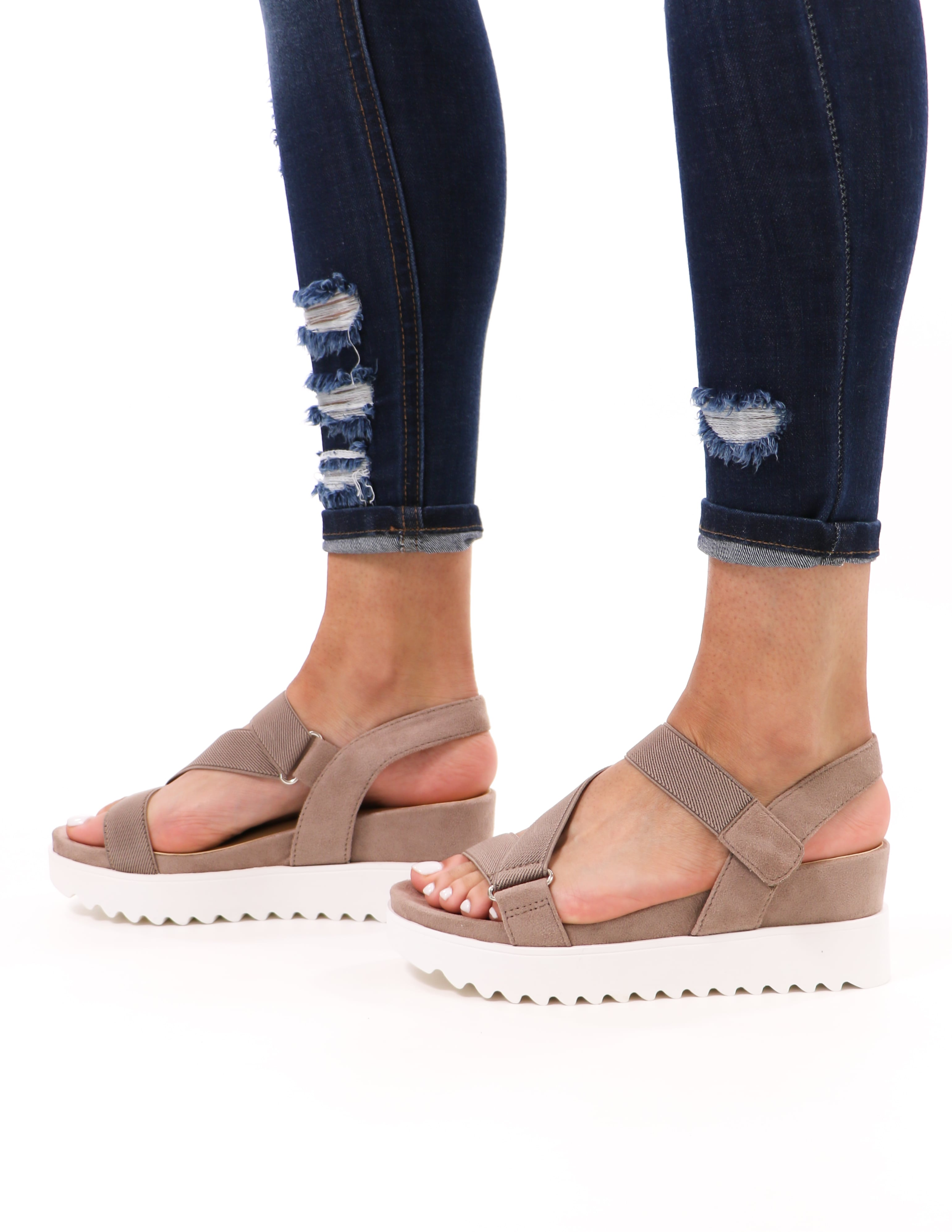 model standing in taupe cubic soda strappy go lucky sandals and distressed denim - elle bleu