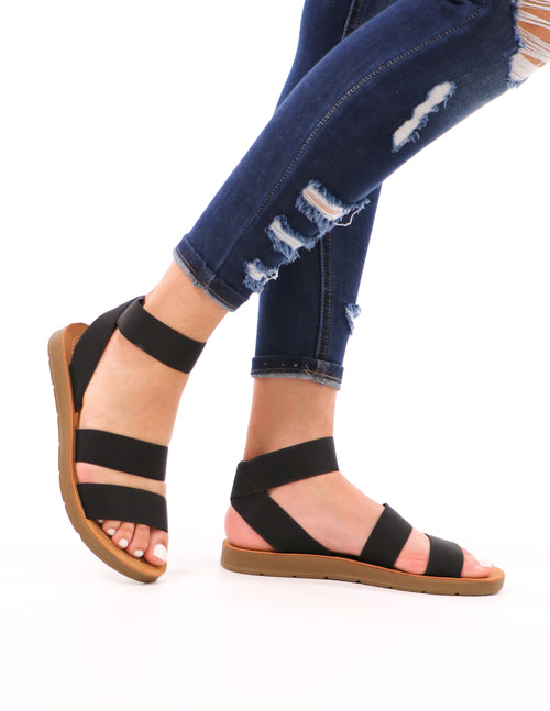 model walking in black elastic cabana sandal and denim