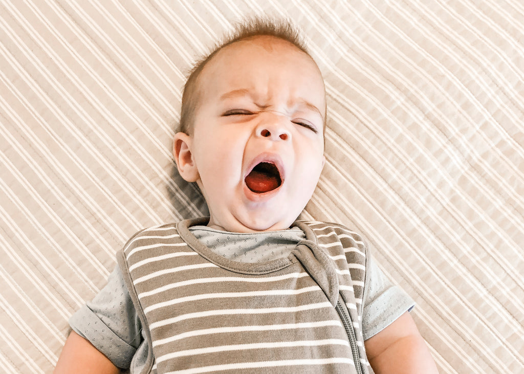 A guide to your baby's sleep patterns blog image of baby yawning in a Woolino sleep bag