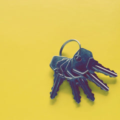 Yellow background with a bunch of silver house keys