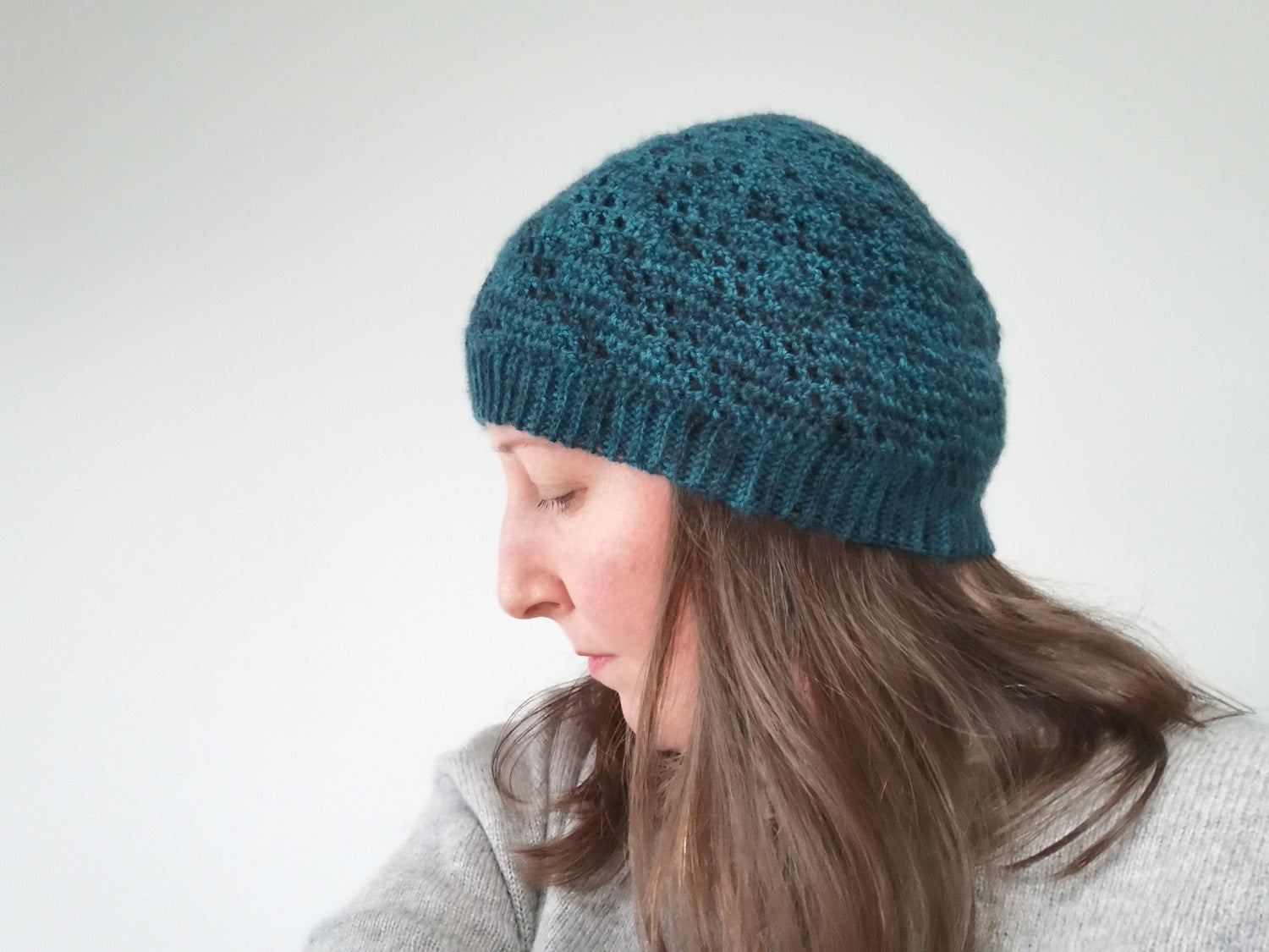 Me wearing my Positivity Spiral Hat pattern.  Its a deep teal variegated colour with lace squares that move around in a spiral.