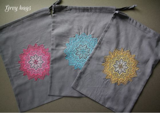 Grey mandala project bags: three grey cotton bags with a mandala on each fading from a dark outside to lighter inner.  L-R the mandalas are pink, turquoise and yellow