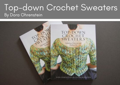 Two copies fo Top-down Crochet Sweaters by Dora Ohrenstein lie on greay background.  The front cover shows the back of a short haired woman with a lacey crocheted top in variegated green yarn.  It has green buttons fastening the back of the cardigan.