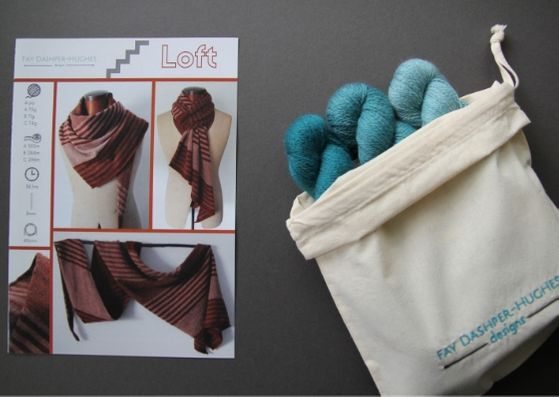 "Knit kit for Loft shawl: on left is a hardcopy of the pattern showing the shawl off in three shades of copper and on the right are the three shades of teal available getting darker from right to left, all sat in a rolled back bag with ""Fay Dashper-Hughes Designs"" embroidered on it."