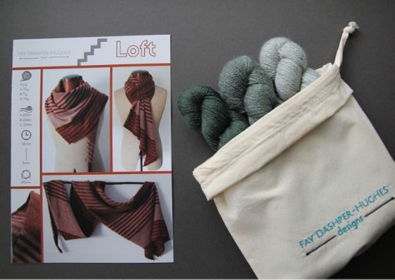 "Knit kit for Loft shawl: on left is a hardcopy of the pattern showing the shawl off in three shades of copper and on the right are the three shades of green available getting darker from right to left, all sat in a rolled back bag with ""Fay Dashper-Hughes Designs"" embroidered on it."