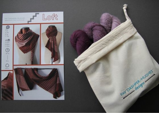 "Knit kit for Loft shawl: on left is a hardcopy of the pattern showing the shawl off in three shades of copper and on the right are the three shades of plum available getting darker from right to left, all sat in a rolled back bag with ""Fay Dashper-Hughes Designs"" embroidered on it."