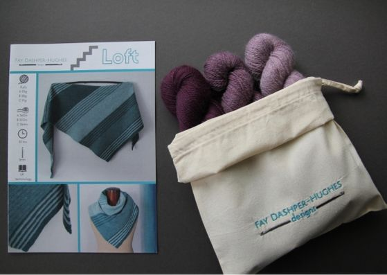 "Crochet kit for Loft shawl: on left is a hardcopy of the pattern showing the shawl off in three shades of teal and on the right are the three shades of plum available getting darker from right to left, all sat in a rolled back bag with ""Fay Dashper-Hughes Designs"" embroidered on it."