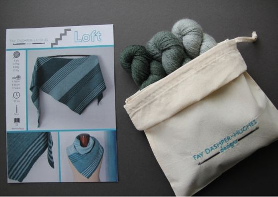 "Crochet kit for Loft shawl: on left is a hardcopy of the pattern showing the shawl off in three shades of teal and on the right are the three shades of green available getting darker from right to left, all sat in a rolled back bag with ""Fay Dashper-Hughes Designs"" embroidered on it."