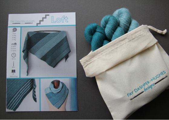 "Crochet kit for Loft shawl: on left is a hardcopy of the pattern showing the shawl off in three shades of teal and on the right are the three shades of teal available getting darker from right to left, all sat in a rolled back bag with ""Fay Dashper-Hughes Designs"" embroidered on it."