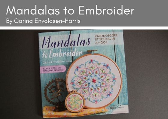 Mandalas to Embroider by Carine Envoldsen-Harris lies ona grey background.  The frony cover shows two mandalas leaning up against a turquoise wooden panel. The small mandala is in an embroidery hoop and features a furled circle design in greens, pink and yellow.  The large mandala is also in an embroidery hoop and shows a floral circular arrangement in blues, pinks and green.