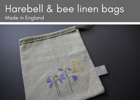 Grey background with natural linen bag, embroidered with purple harebells, a yellow sprig of grass and a bumple bee.