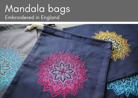 Embroidered mandala project bags:  three navy bags on top of a grey one.  Each has a machine embroidered mandala on it in various colurs (pink, yellow or turquoise).  The mandalas change shade going from a darker outer to a lighter inner.
