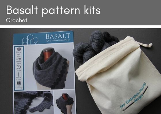 "Basalt crocheted shawl kit: on the left lies a hardcopy of the pattern showing the shawl in two shades of grey, the darkest is used for the hexagonal edging.  To the right is a folded down bag with embroidery saying ""Fay Dashper-Hughes Designs"".  Inside the bag are two large skeins of a mid-grey Merino wool and a mini skein of a charcoal grey Merino wool."