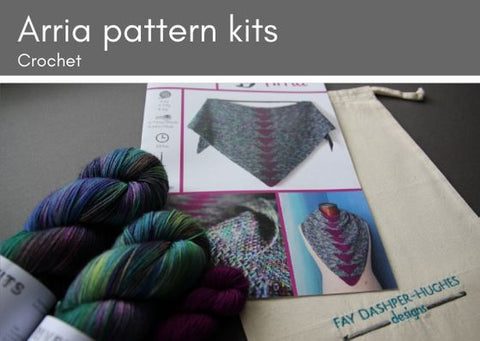 "Arria crocheted shawl kit: two skeins of variegated wool (pinks, purples, greens, teals and blues) lie on top of a pattern for the shawl which is on top ofa cotton bag with ""Fay Dashper-Hughes Designs"" embroidered on it."