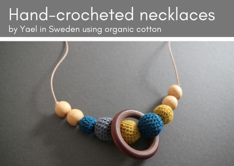 Hand-made crocheted necklace on a grey background. Some wooden beads are threaded onto the leather thng bare and others have been crocheted with organic cotton in grey, dark teal and mustard.  The keather thing is nude in colour.
