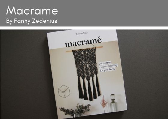 Macrame book by Fanny Zedenius lies on a grey background.  The frony cived shows a black macrame wall hanging against a cream wall with plants and a bottle featured beneath.  the macrame hangs off a wooden dowl rod.