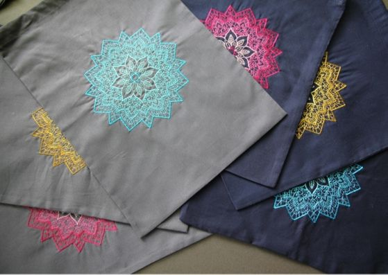 Embroidered mandala project bags: three grey ones on the left and three navy bags on the right.  Each bag has an embroidered manadala on it and the colours are either pink, yello or turquoise.